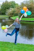 Girl standing at pond with colored balloons