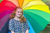 Teenage girl under umbrella with various colors