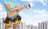 Woman in tool belt counting on calculator. Building and sky as backdrop