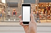 stock photo of shopping center  - Smartphone with empty screen in woman hand in a shopping center  - JPG