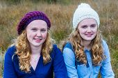 Two teenage girls wearing hats in nature