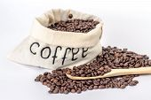 textile bag full of coffee beans and wooden spoon isolated