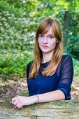 Portrait of red-haired teenage girl in forest