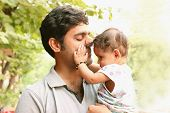 Indian Father holding daughter lovingly. Nature background