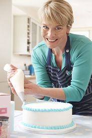foto of icing  - Woman Icing Birthday Cake In Kitchen At Home - JPG