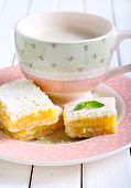 stock photo of icing  - Tangy lemon squares with icing sugar and cup of coffee - JPG