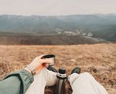 stock photo of pov  - Traveler man sitting with cup of tea and thermos in the mountains - JPG