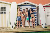 image of beach hut  - Group of young people in swimsuit with surfboards having fun in a summer day over a beach striped huts background - JPG