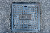 stock photo of spqr  - Iron roman manhole cover on the street with spqr word - JPG