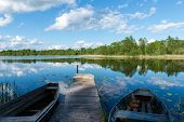 picture of bent over  - White clouds on the blue sky over blue lake with reflections with boats and boardwalk - JPG