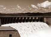 pic of dam  - Black and white view from one side of the wall of famous Gariep Dam near Norvalspont in South Africa with open spillway and picturesque landscape in the background - JPG