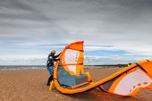 foto of kites  - Kite surfer wearing a wetsuit is preparing his kite on a windy cold day - JPG