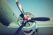 image of propeller plane  - part of the plane with the propeller closeup in retro tones and a place for the text in the sky - JPG