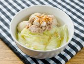 stock photo of thai cuisine  - Thai Cuisine and Food Bowl of Delicious Lettuce with Minced Pork and Fish Meat Ball Soup Topping with Fried Garlic - JPG