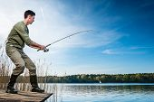 image of catch fish  - Fisherman catching fish angling at the lake under a blue sky - JPG