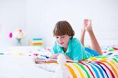 foto of homework  - School age boy reading a book in bed - JPG