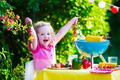 stock photo of bbq party  - Children grilling meat. Family camping and enjoying BBQ. Little girl at barbecue preparing steaks kebab and corn. Kids eating grill and healthy vegetable meal outdoors. Garden party for toddler child