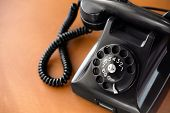 stock photo of rotary dial telephone  - Old fashioned retro rotary dial phone on wooden desk closeup - JPG