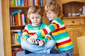 stock photo of daycare  - Two little siblings kid boys making photos with photocamera indoors - JPG