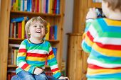 picture of daycare  - Two funny little kids making photos with photocamera indoors - JPG