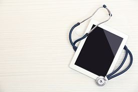 picture of stethoscope  - Medical tablet with stethoscope on wooden background - JPG
