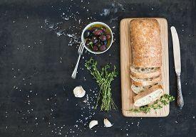 image of fresh slice bread  - Italian ciabatta bread cut in slices on wooden chopping board with herbs - JPG