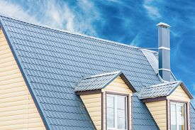 stock photo of red roof  - chimney on the roof of the house against the blue sky - JPG