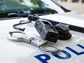 Police equipment on a  police car.  Handcuffs, baton and pager on top of a police car. Selective foc poster