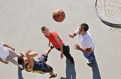 group of young boys who playing basketball outdoor on street with long shadows and bird view perspec