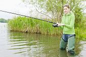 picture of fisherwomen  - young woman standing and fishing in pond - JPG