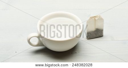 poster of Mug Filled With Boiling Water And Teabag On White Background. Tea Time Concept. Cup Or White Porcela