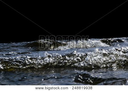 poster of Big Windy Waves Splashing Over Rocks. Wave Splash In The Lake Isolated On Black Background. Waves Br