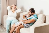 The Husband And Wife And A Small Child Sitting On The Couch In The Room. The Wife Holds Her Head And poster