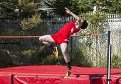 A High School Male Is Over The Bar In The High Jump With A Red Uniform On And Red Matts To Land On. poster