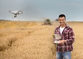 Farmer With Drone In Front Of Combine Harvester poster