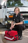 Portrait of a happy paramedic kneeling by a portable oxygen unit and ambulance