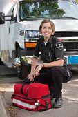 Retrato de un paramédico feliz de rodillas en una unidad de oxígeno y una ambulancia