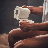 Close Up. Handsome Young Afro American Man Sitting On Toilet With Toilet Paper At Morning. Personal  poster