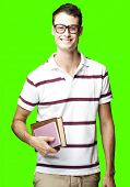 portrait of young man smiling and holding books against a removable chroma key background
