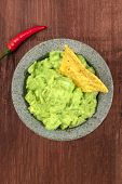 An Overhead Photo Of Guacamole Sauce In A Molcajete, Traditional Mexican Mortar, With A Nacho, Torti poster