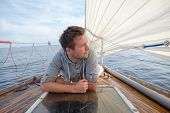 Young European Man Sitting On Yacht Looking At Sea. Travelling On Old Boat With Sail. Concept Of Fre poster