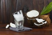 Coconut Milk Glass With Coconut Half And Coconut Pieces And Leaf  On Wooden Table. poster