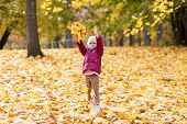 childhood, season and people concept - happy little girl playing with fallen leaves at autumn park poster