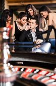 Young handsome male with cigar surrounded by four beautiful women in casino