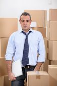 Man in storage depot surrounded by boxes