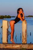 A beautiful hispanic brunette model enjoying the morning sun at sunrise poster