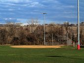 Softball Field - Sports Venue With Light Towers And Scenic Blue Sky And Clouds. poster