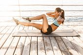 Image of healthy fitness woman 20s in sportswear lying on exercise mat near seaside and doing cardio poster
