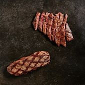 Hot Juicy Whole Machete Steak and Denver Steak on Barbecue Grill Background. Fresh Medium Rare Beef  poster