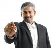 Mature adult Asian Indian man arm out holding a new key over white background